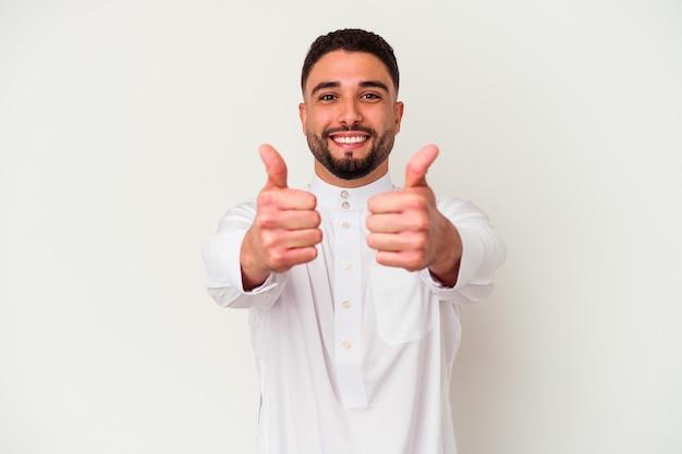 白い背景に典型的なアラブの服を着た若いアラブ人男性が、親指を上げ、何かを応援し、コンセプトをサポートし、尊重する。