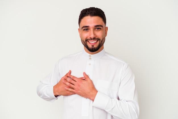 흰 벽에 고립 된 전형적인 아랍 옷을 입고 젊은 아랍 남자는 가슴에 손바닥을 눌러 친근한 표현을 가지고 있습니다. 사랑 개념.