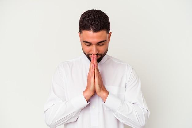 口の近くで祈って手をつないで白い壁に隔離された典型的なアラブの服を着ている若いアラブ人は、自信を持っています。
