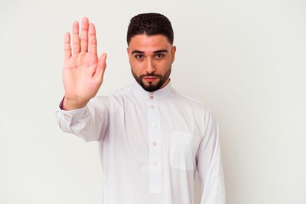 Молодой арабский человек, носящий типичную арабскую одежду, изолированную на белой стене, стоящей с протянутой рукой, показывая знак остановки, предотвращая вас.
