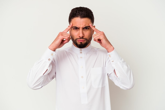 Young arab man wearing typical arab clothes isolated on white background focused on a task, keeping forefingers pointing head.