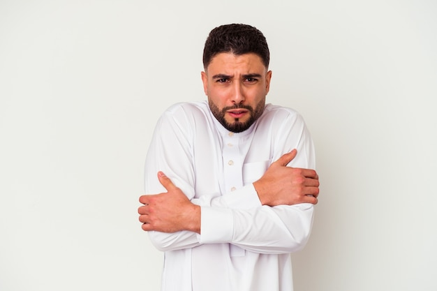 Young arab man wearing typical arab clothes isolated on white going cold due to low temperature or a sickness.
