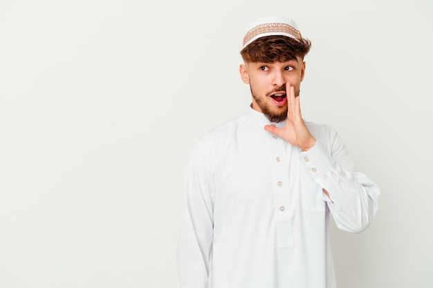 Young arab man wearing the typical arabic costume isolated on white is saying a secret hot braking news and looking aside