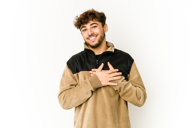 Young arab man on white background has friendly expression, pressing palm to chest. love concept.