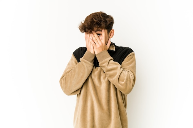 Young arab man on white wall blink through fingers frightened and nervous