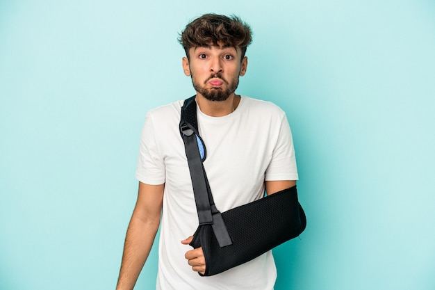 Young arab man with broken hand isolated on blue background shrugs shoulders and open eyes confused.