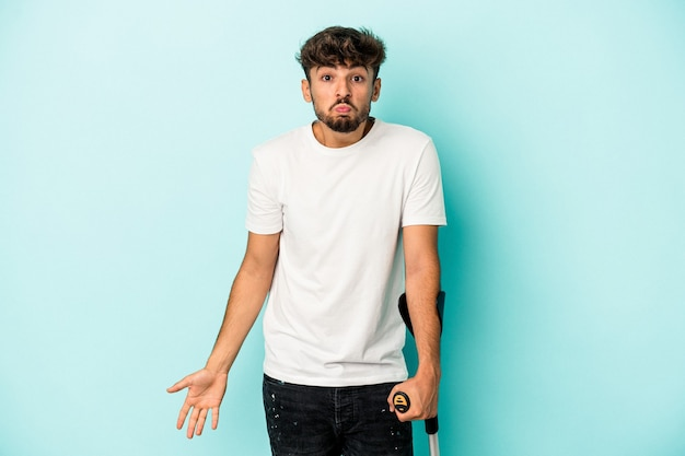 Young arab man with crutches isolated on blue background shrugs shoulders and open eyes confused.
