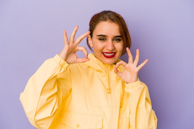 Young arab mixed race woman cheerful and confident showing ok gesture.