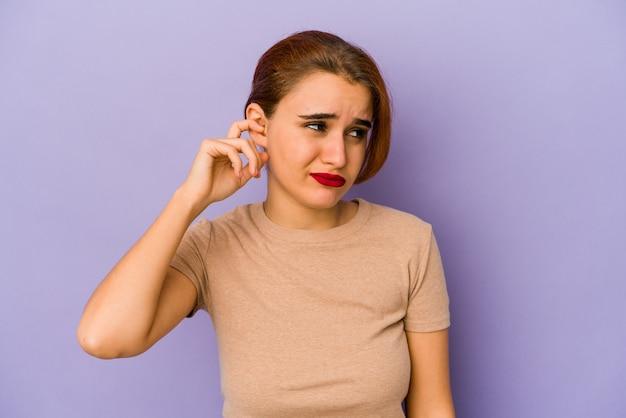 耳を指で覆い、大声で周囲にストレスを感じ、必死になっている若いアラブの混血の女性。