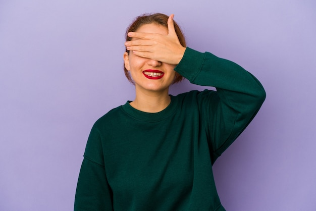 Young arab mixed race woman covers eyes with hands, smiles broadly waiting for a surprise.