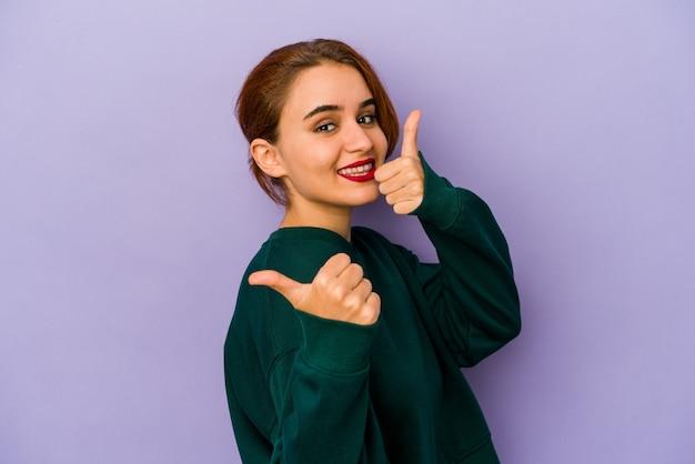 Молодая арабская женщина смешанной расы поднимает большие пальцы руки вверх, улыбается и уверенно.