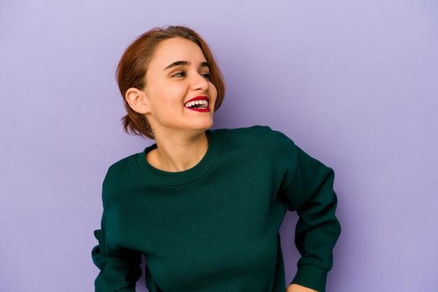 Молодая арабская женщина смешанной расы расслаблена и счастлива смеется, вытянув шею, показывая зубы.
