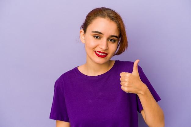 Young arab mixed race woman smiling and raising thumb up