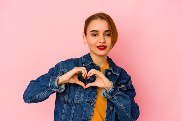 Young arab mixed race woman smiling and showing a heart shape with hands.