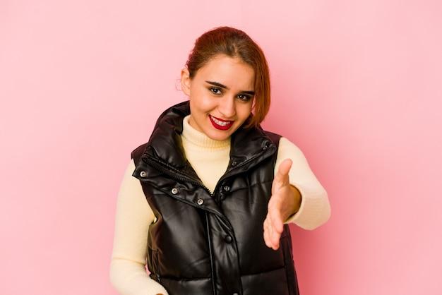 挨拶ジェスチャーでカメラに手を伸ばす若いアラブ混血の女性。