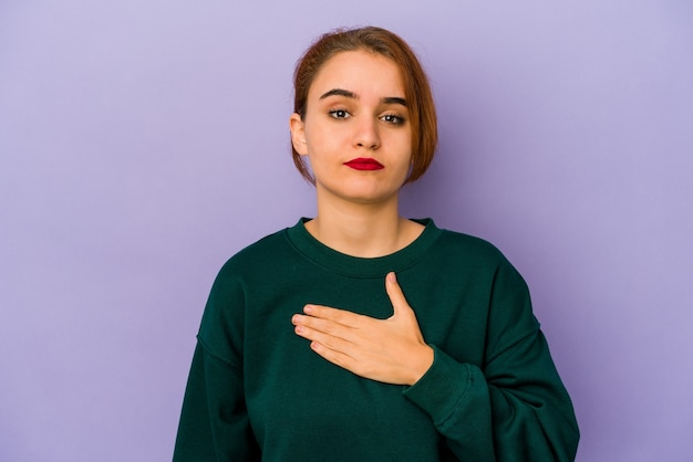 Young arab mixed race woman taking an oath, putting hand on chest