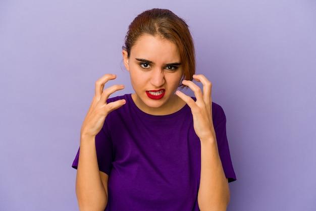 Молодая арабская женщина смешанной расы расстроена криком с напряженными руками.