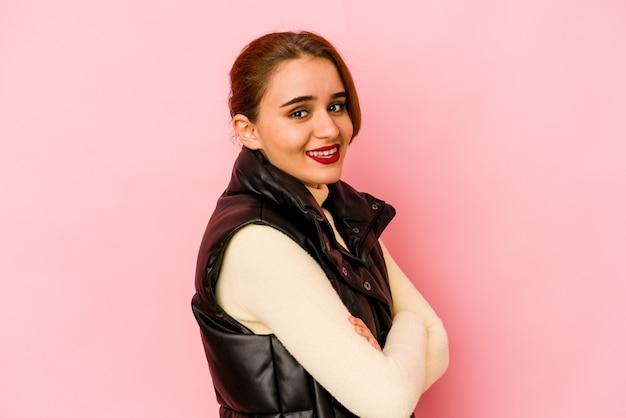 自信を持って、決意を持って腕を組んでいる若いアラブ混血の女性。