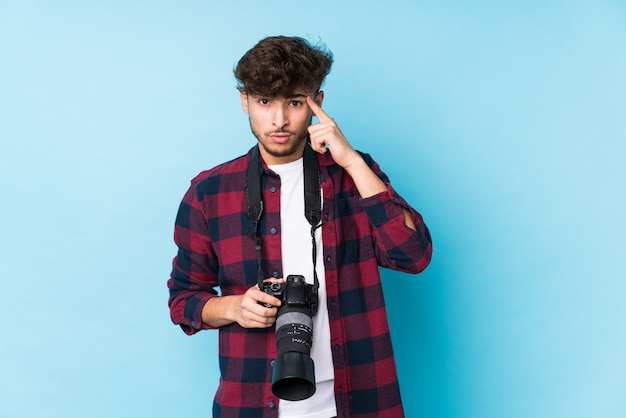 Young arab photographer man showing a disappointment gesture with forefinger.