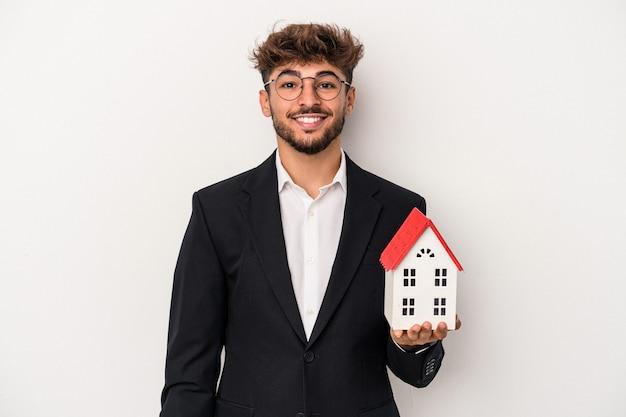 孤立した背景に隔離されたモデルハウスを保持している若いアラブの不動産の男は幸せ、笑顔、陽気な。