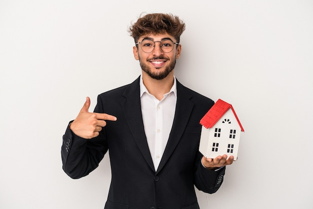 Young arab real estate man holding a model house isolated on isolated background person pointing by hand to a shirt copy space, proud and confident