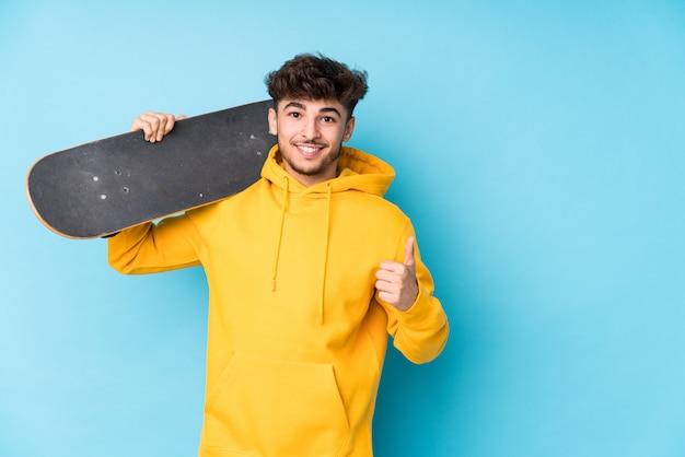 Young arab skater man isolated smiling and raising thumb up
