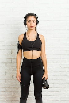 Young arab sporty woman listening to music and holding a dumbbell