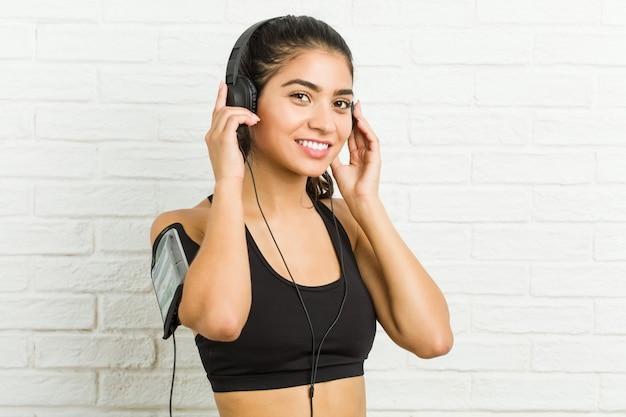 Молодая арабская спортивная женщина слушает музыку