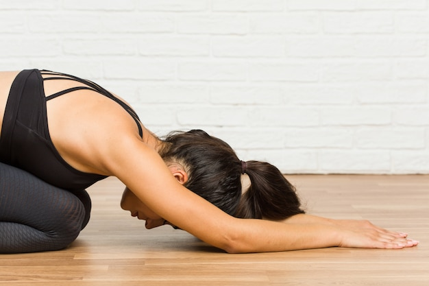 Young arab sporty woman practicing yoga on the floor