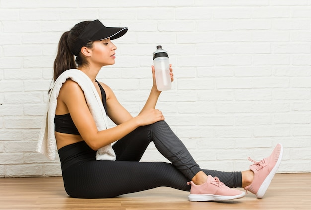 Young arab sporty woman sitting and drinking water
