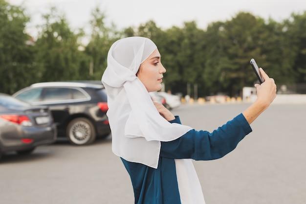 야외에서 스마트폰으로 셀카를 만드는 머리 스카프를 두른 젊은 아랍 학생 소녀.