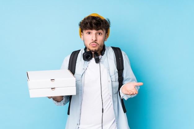 Молодой арабский студент-мужчина, держащий пиццу, пожимает плечами и смущает открытые глаза.