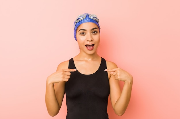 Young arab swimmer woman isolated surprised pointing with finger, smiling broadly.