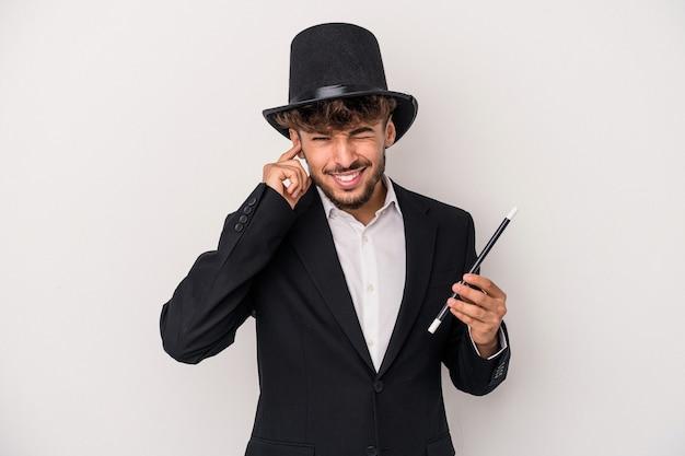 手で耳を覆う白い背景で隔離の杖を保持している若いアラブの魔法使いの男。