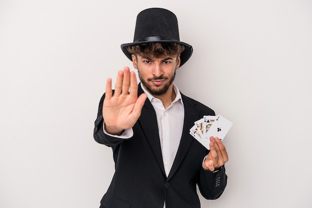 Young arab wizard man holding a magic cards isolated on white background standing with outstretched hand showing stop sign, preventing you.