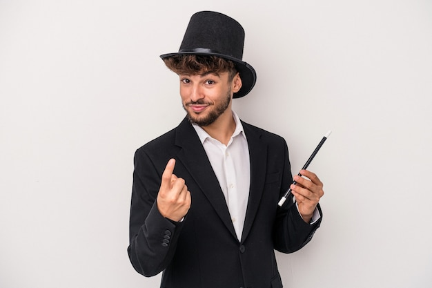 Young arab wizard man holding a wand isolated on white background pointing with finger at you as if inviting come closer.