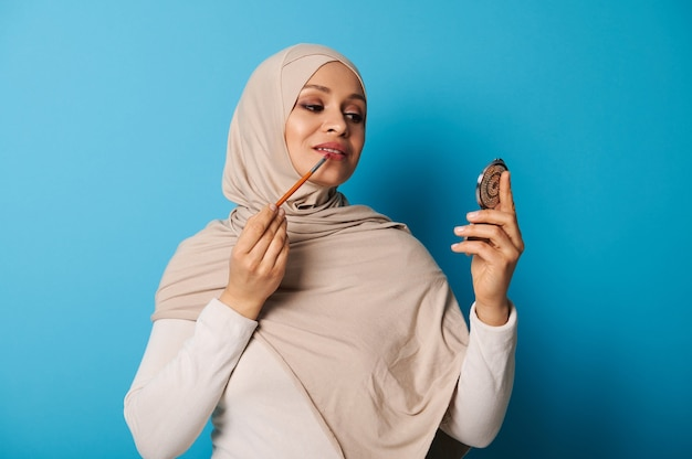 Young arab woman in beige hijab uses a makeup brush to apply lipstick to her lips and looks at her reflection in a small cosmetic mirror. isolated portrait