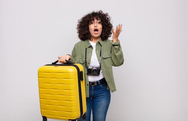 젊은 아랍 여성이 행복하고 놀랍고 쾌활한 느낌, 긍정적 인 태도로 웃고 솔루션 또는 아이디어 여행 개념을 실현합니다.