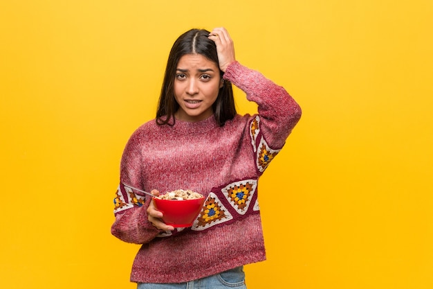 Young arab woman holding a cereal bowl being shocked, she has remembered important meeting.