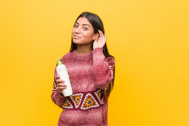 Young arab woman holding a cream bottle trying to listening a gossip.