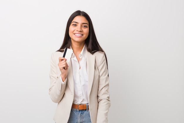 Young arab woman holding a credit card happy, smiling and cheerful.