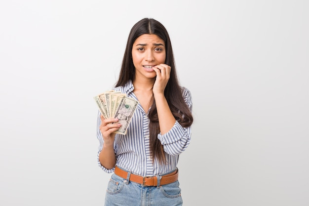 Young arab woman holding dollars biting fingernails, nervous and very anxious.