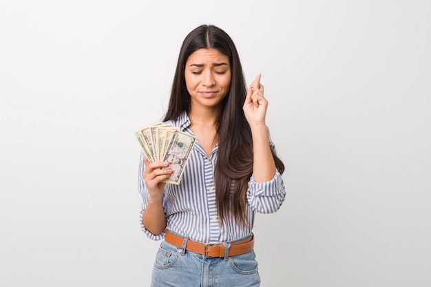 Young arab woman holding dollars crossing fingers for having luck