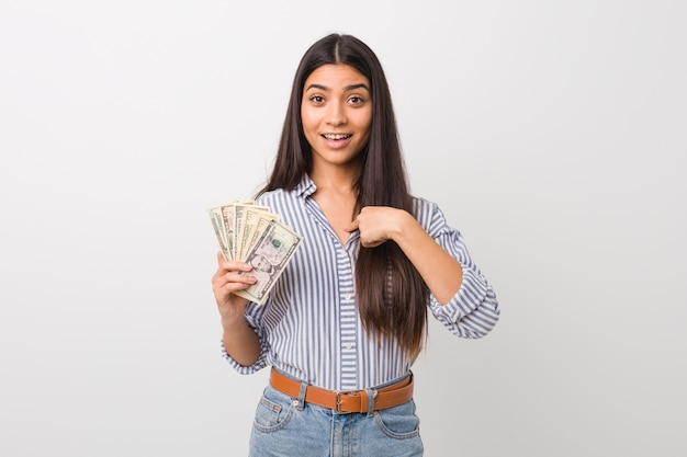 Young arab woman holding dollars surprised pointing at himself, smiling broadly.