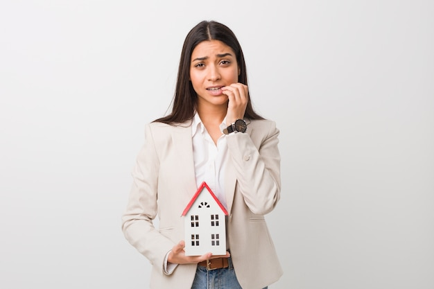 Young arab woman holding a house icon biting fingernails, nervous and very anxious.