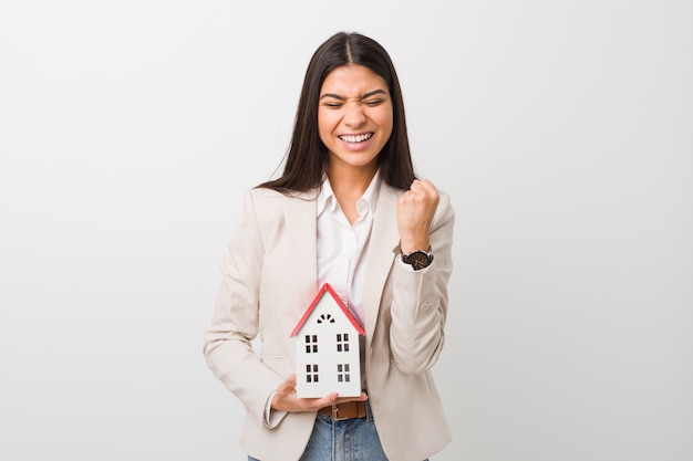 Young arab woman holding a house icon cheering carefree and excited. victory concept.