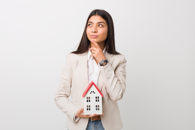 Young arab woman holding a house icon looking sideways with doubtful and skeptical expression.