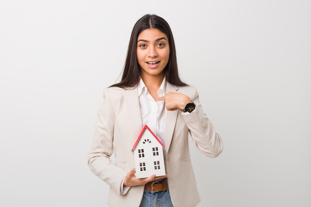 Young arab woman holding a house icon surprised pointing at himself, smiling broadly.