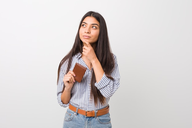 Young arab woman holding a wallet looking sideways with doubtful and skeptical expression.