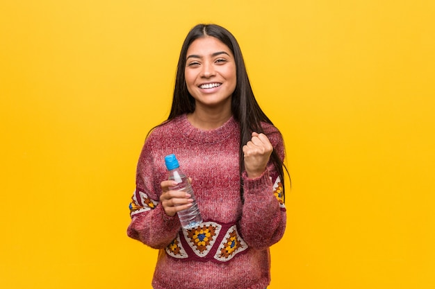 Young arab woman holding a water bottle cheering carefree and excited. victory concept.